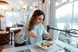 canvas print picture - Smiling woman eating fresh salad in restaurant