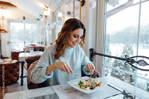 Smiling woman eating fresh salad in restaurant