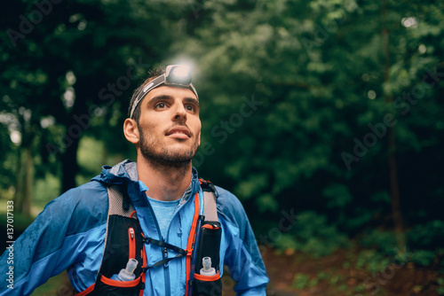 Obraz Fit male jogger with a headlamp rests during training for cross country trail race in nature park. - fototapety do salonu