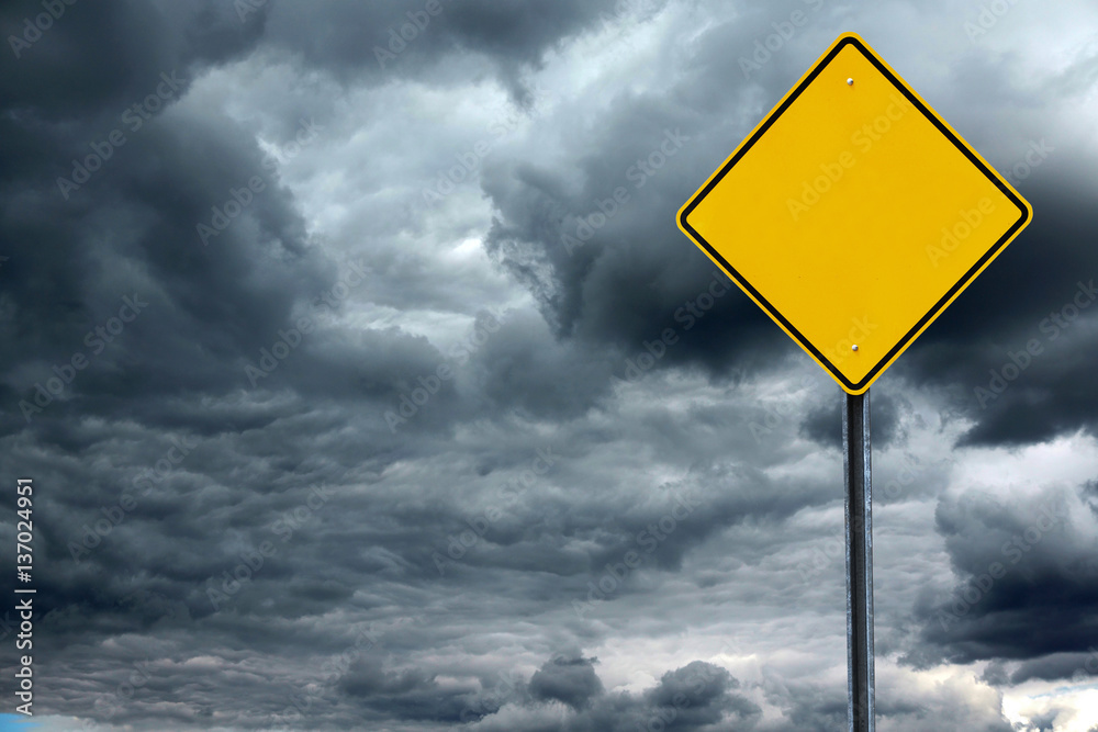 Fototapeta blank road warning sign in front of storm cloud background, ready for text
