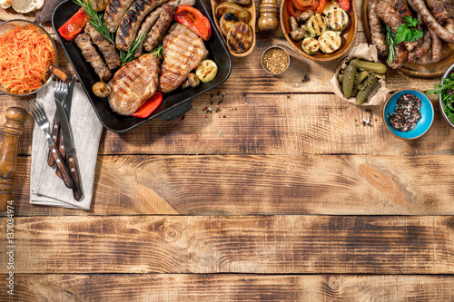 Aluminium Prints Grill / Barbecue Different foods cooked on the grill on the wooden table