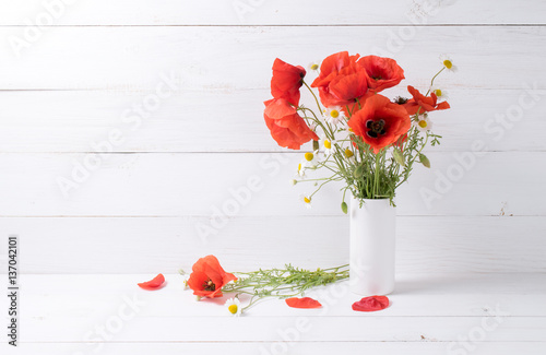 Poster Poppy Poppies and daisy in vase on background of shabby wooden planks