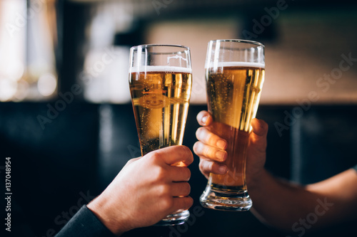 Cheers. Close-up of two men in shirts toasting with beer at the bar counter
