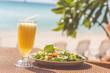 Seafood salad, orange fresh juice on the table near sea