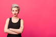 Leinwandbild Motiv confident woman standing with arms crossed isolated over pink background