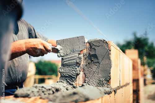 Fototapeta Bricklayer construction worker installing brick masonry on exterior wall with tr