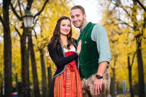 Fotografía  Mann und Frau mit bayrischer Tracht in vertrauter Pose, stehend vor herbstlicher