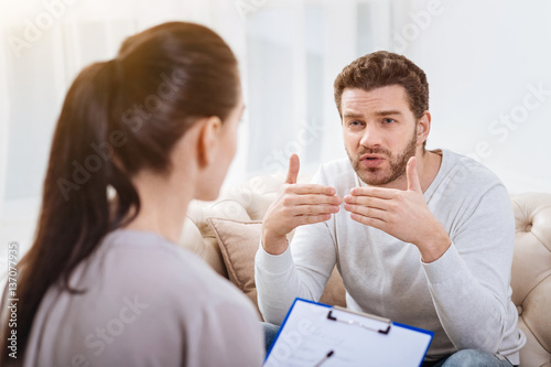 Nice bearded man talking to the psychologist