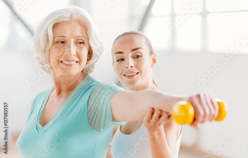 Fotografia  Delighted pleasant woman exercising with a dumbbell