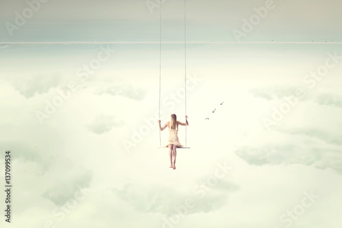 Obraz upside down surrealistic minimal woman swings in the air - fototapety do salonu