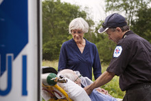 Paramedic And Senior Woman Standing Next To Senior Patient Lying On Stretcher