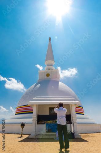 Man In White Shirt Worships Stupa Dagabo Wrapped With Buddhist Flag Under Sun Shining Blue