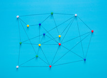 Small Network Of Pins (Thumbtack)and String, An Arrangement Of Colourful Pins Linked Together With String On A Pale Background Suggesting A Network Of Connections.
