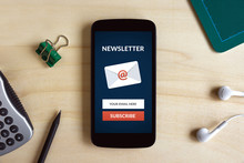 Subscribe Newsletter Concept On Smart Phone Screen On Wooden Desk. All Screen Content Is Designed By Me. Flat Lay