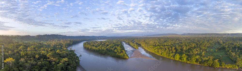 Fototapeta Aerial panorama of the Rio Napo at dawn in the Ecuadorian Amazon with the first rays of the sun illuminating the forest canopy.