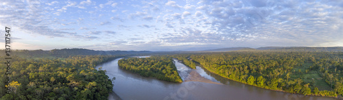 Fototapeta Aerial panorama of the Rio Napo at dawn in the Ecuadorian Amazon with the first rays of the sun illuminating the forest canopy. obraz