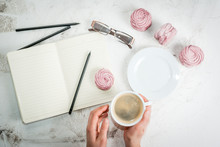 Home Spring Vacation, Relax, Work. White Stone Concrete Desk With Notepads, Coffee And Pink Berry Pastries (marshmallows). The Girl Holds A Cup In His Hands Top View Copy Space