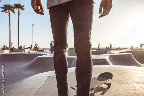 Male skateboarder preparing to launch at skate park, Venice Beach, California, U Poster