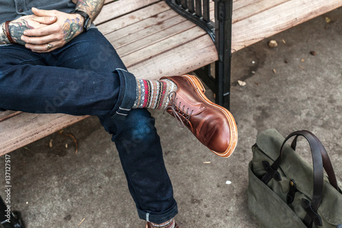 Man sitting on bench, waist down, with casual clothing and accessories