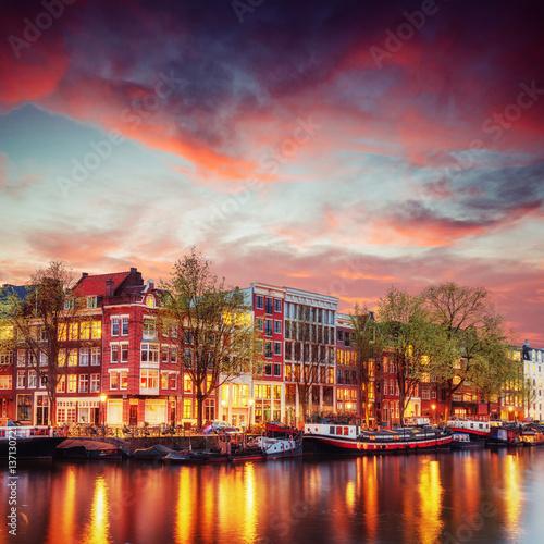 kanal-w-amsterdamie-plynacy-kolo-kolorowych-kamienic-na-tle-rozowego-wieczornego-nieba