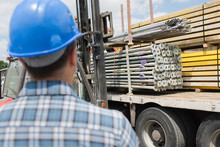 Rear View Of Man Looking At Lorry Load Of Materials