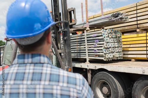 Valokuva  Rear view of man looking at lorry load of materials