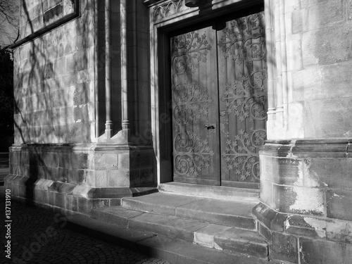 Deurstickers Rudnes Schön verzierte alte Kirchentür der Herz-Jesu-Kirche in Münster in Westfalen im Münsterland, aufgenommen in traditionellem Schwarzweiss