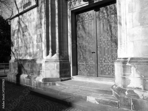 Deurstickers Rudnes Kunstvoll verzierte Kirchentür an einer katholischen Pfarrkirche in Münster in Westfalen im Münsterland, aufgenommen in traditionellem Schwarzweiss