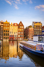 Traditional Old Buildings And Boats At Sunset In Amsterdam, Netherlands.