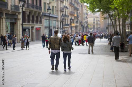 obraz PCV Couple walking down the streets of Barcelona, Spain. Light tilt shift effect.