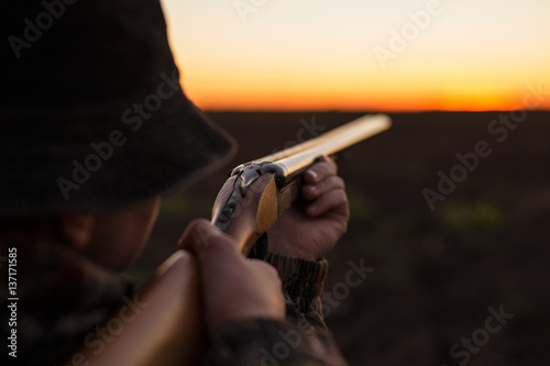 Fotobehang Jacht Hunter aiming shotgun in dusk