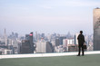 Business man after work standing on rooftop and looking city,business concept
