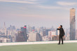 Business man standing on rooftop and talking mobile phone looking city,business concept