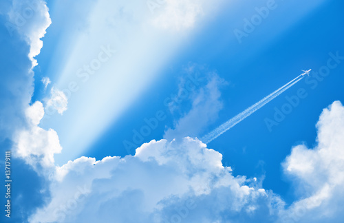 Poster Avion à Moteur Airplane flying in the blue sky among clouds and sunlight