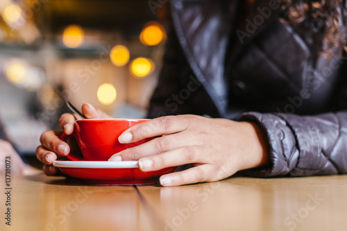Woman Holding a Coffee in a Restaurant