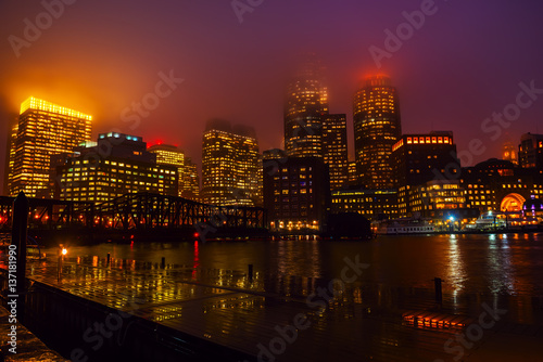 Sticker - View of Boston skyscrapers night.  The tops of the buildings in the fog and haze. Rainy foggy weather, brilliant paving and lights of skyscrapers.