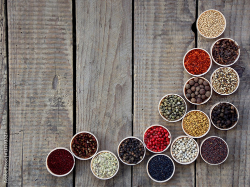 Canvas Prints Spices spices on a wooden background. Coriander, black pepper, paprika, mustard, turmeric, cumin, sumac, fenugreek, cloves, cubeb.