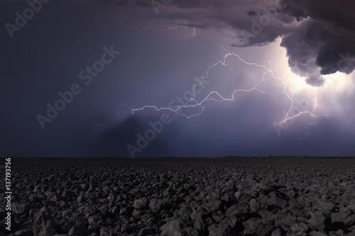 Valokuva  Thunderstorm with lightning in plowed field