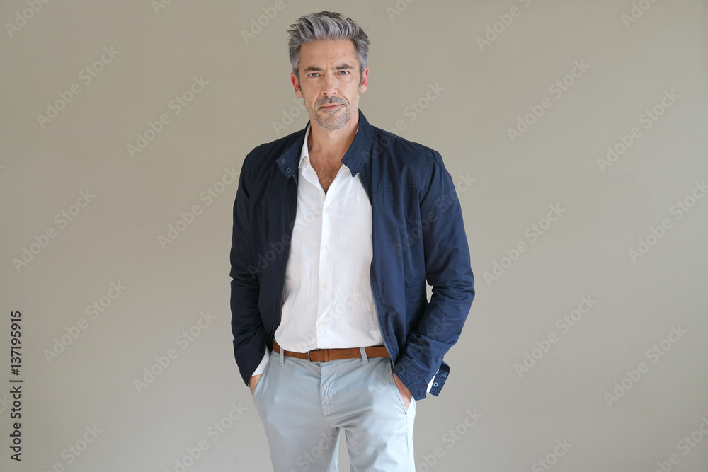 Fototapeta Handsome mature man standing on grey background, isolated