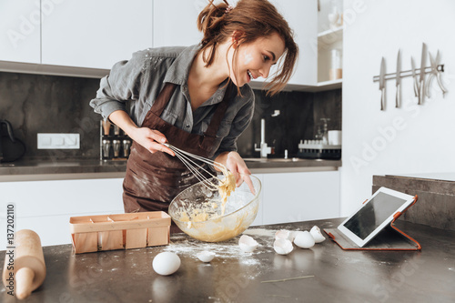 Cheerful woman cooking and looking at tablet computer. Fototapeta