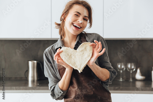 Fotografie, Obraz  Cheerful lady holding the dough heart.