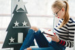 Blonde lady in black glasses reads book sitting before wooden Christmas tree on balcony