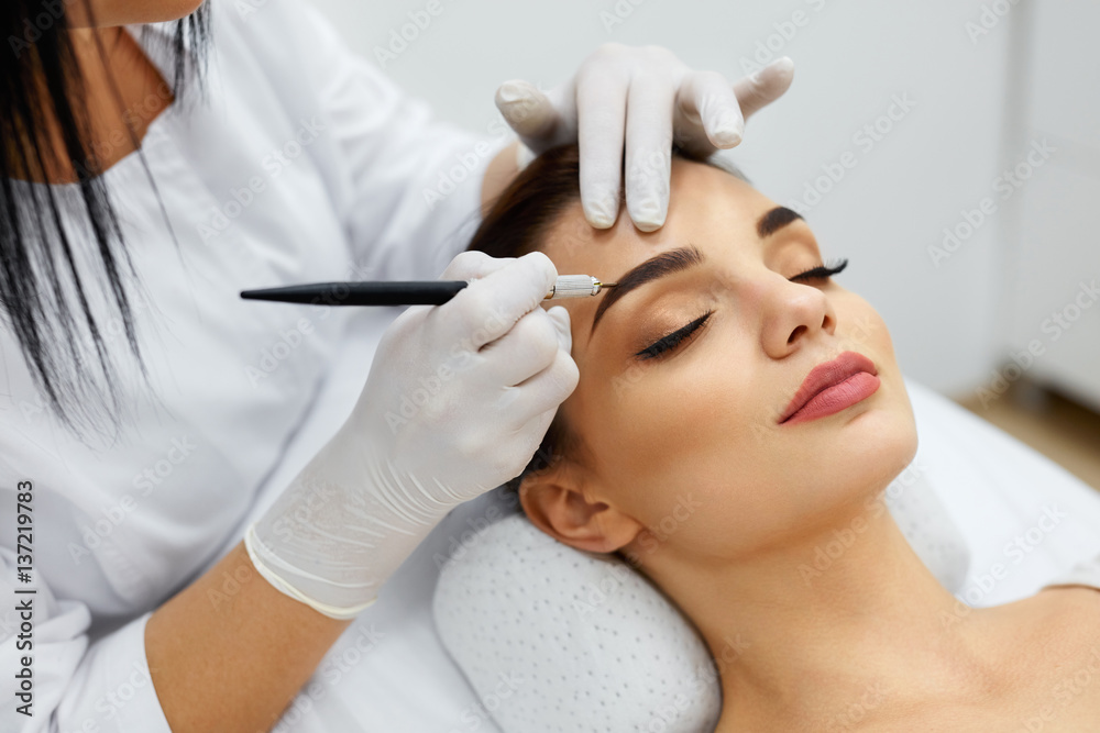 Fototapety, obrazy: Beautician Doing Permanent Eyebrows Makeup Tattoo On Woman Face
