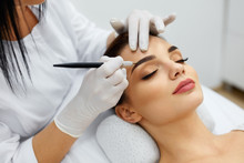 Beautician Doing Permanent Eyebrows Makeup Tattoo On Woman Face