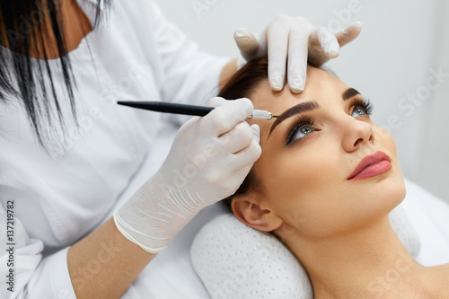 Beautician Doing Permanent Eyebrows Makeup Tattoo On Woman Face Fototapet