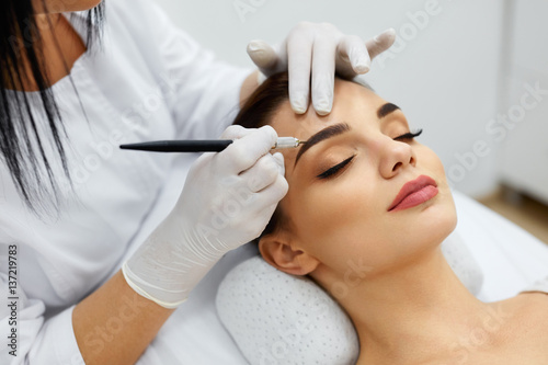 Fotografering  Beautician Doing Permanent Eyebrows Makeup Tattoo On Woman Face