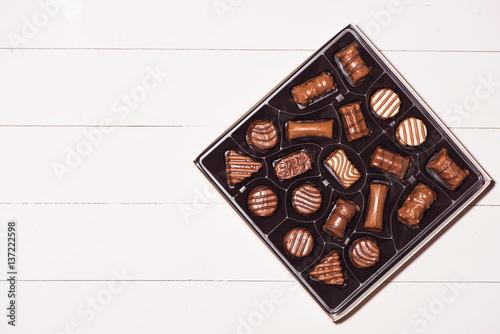 Plakat widok z góry różnych czekoladowe pralinki w polu na białym tle drewnianych.