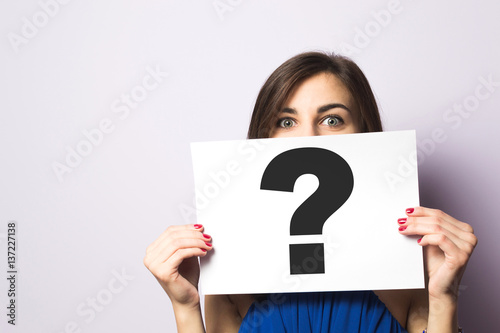 Fotografia Girl holding a signboard with a question mark