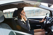 Attractive businesswoman talking on the phone while driving a car.She hurries on business meeting.