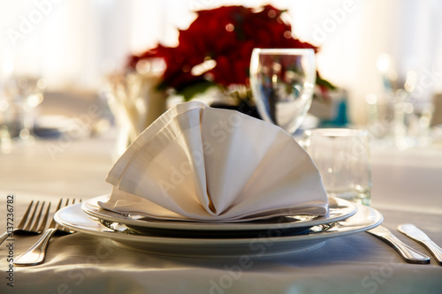 Fotografie, Obraz  Linen napkin on a plate on the table covered with a white tablecloth